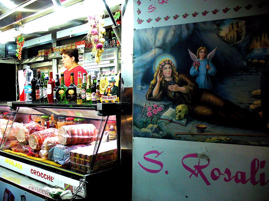 "A night food kiosk in Palermo (Sicily, Italy), displaying a poster of the city's patron saint, Santa Rosalia or ""Santuzza"". Palermo celebrates its patron saint in July."