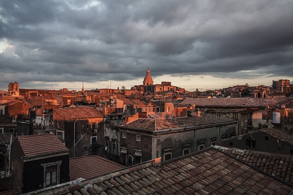 The sun rises over the roofs of Catania