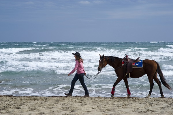 woman and horse on a beach in Italy